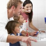 Dentist in Carson City - Family In Bathroom Brushing Teeth - DentistCarsonCity.com